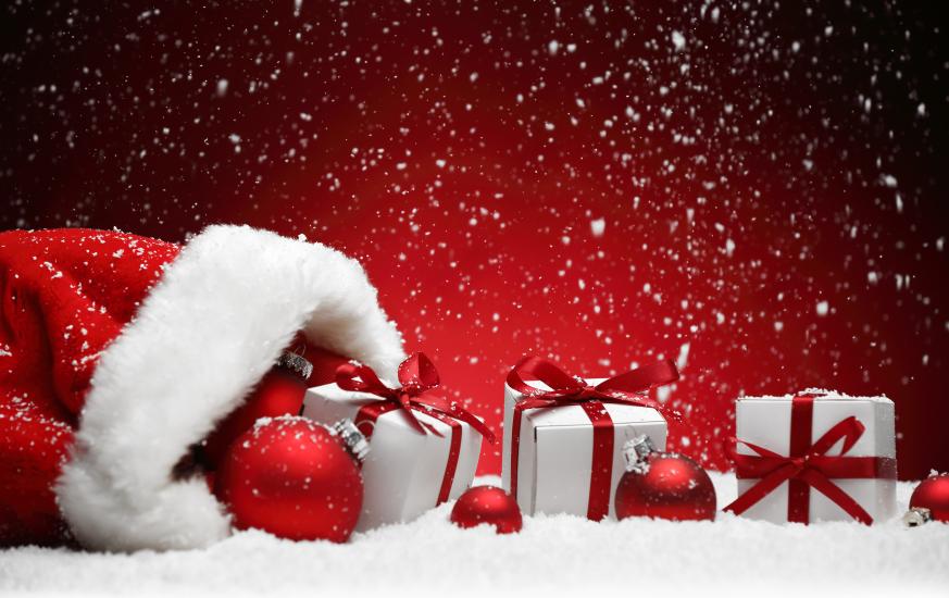 Na czerwonym tle padający śnieg z przodu prezenty zapakowane w biały papier z czerwoną wstążką, czerwone bombki. Z lewej strony czapka Mikołaja