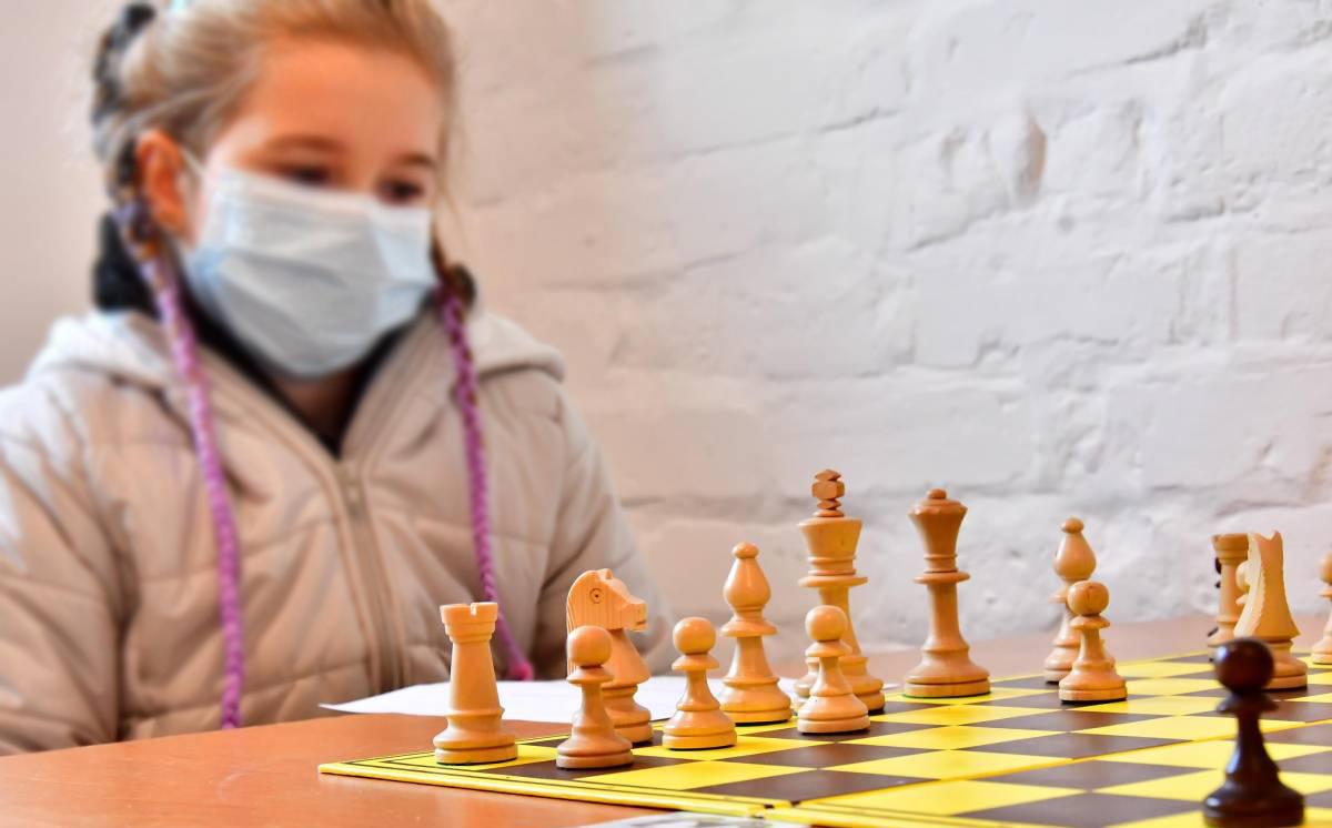 Na pierwszym planie plansza oraz figury szachowe, na drugim planie dziewczynka z maseczką siedząca przy stole