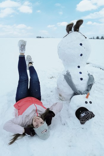 Na zdjęciu bałwana do góry nogami oraz uśmiechnięta dziewczyna- również do góry nogami. Bałwan ma czapkę z daszkiem, szary szalik oraz buty. Dziewczyna z rękoma pod głową z uniesionymi do góry nogami. W tle piękna zimowa aura