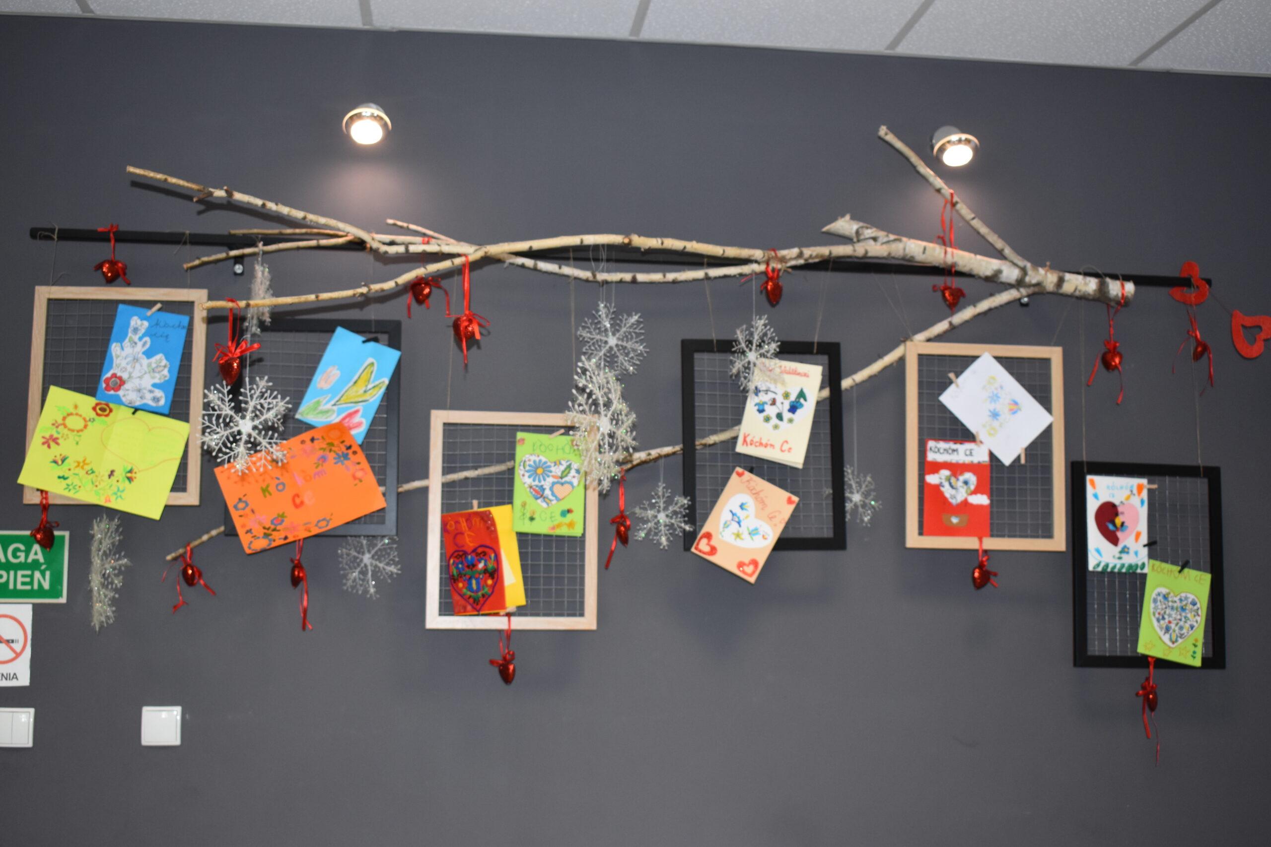 Zdjęcia 12 walentynek, które są obwwieszone na gałęzi, obok prac widać czertwone serduszka, również zawieszone na gałęzi. Wszystko to jest na granatowej ścianie