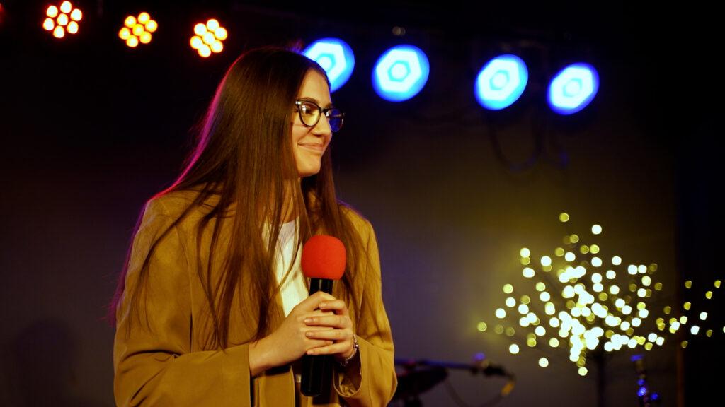 Uśmiechnięta wokalistka Zuzanna Zaborowska. W tle widać oświetlenie sceny
