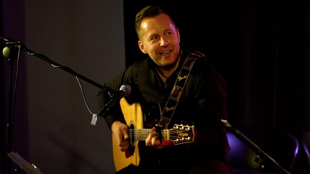 Adam Szewczyk grający na gitarze akustycznej