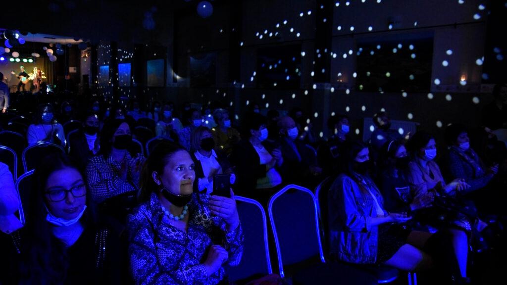 Zgromadzona publiczność w sli GOKSiR . Wszyscy maja założone maseczki ochronne na twarzach