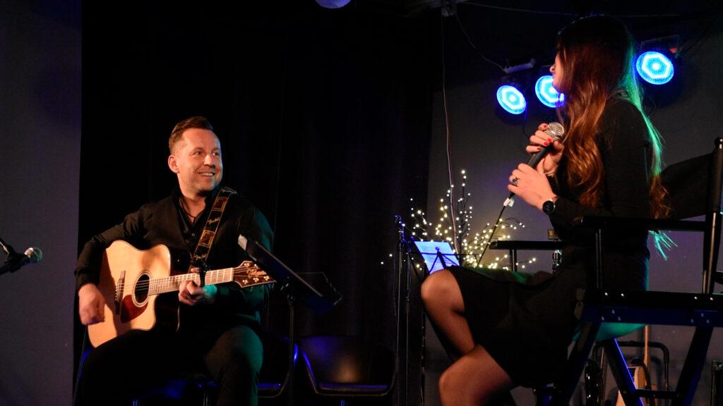 Z lewej Adama Szewczyk grający na gitarze z prawej strony Katarzyna Błaszczyk. W tle oświetlenie sceniczne.