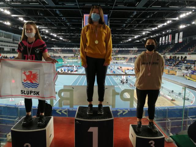 Trzy osoby stojące na podium w tle widać bieżnie lekkoatletyczną oraz trybuny