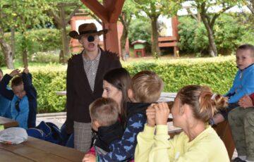Grupa dzieci która ogląda przedstawienie oraz osoba przebrana w strój teatralny